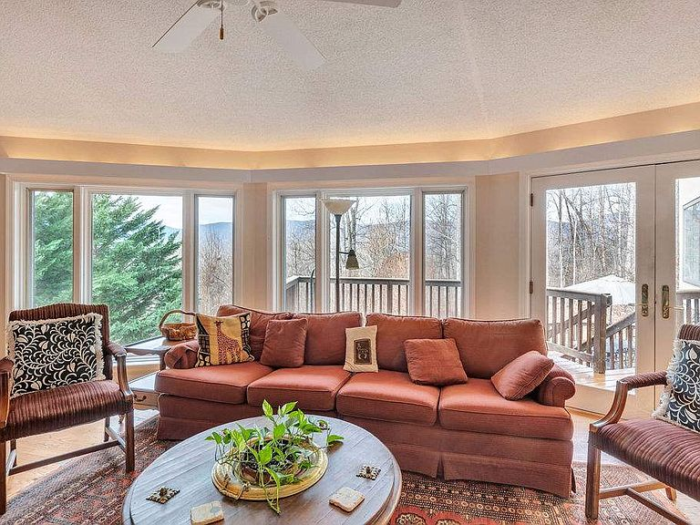 cotw around around, round top living room with wall of window and deck access