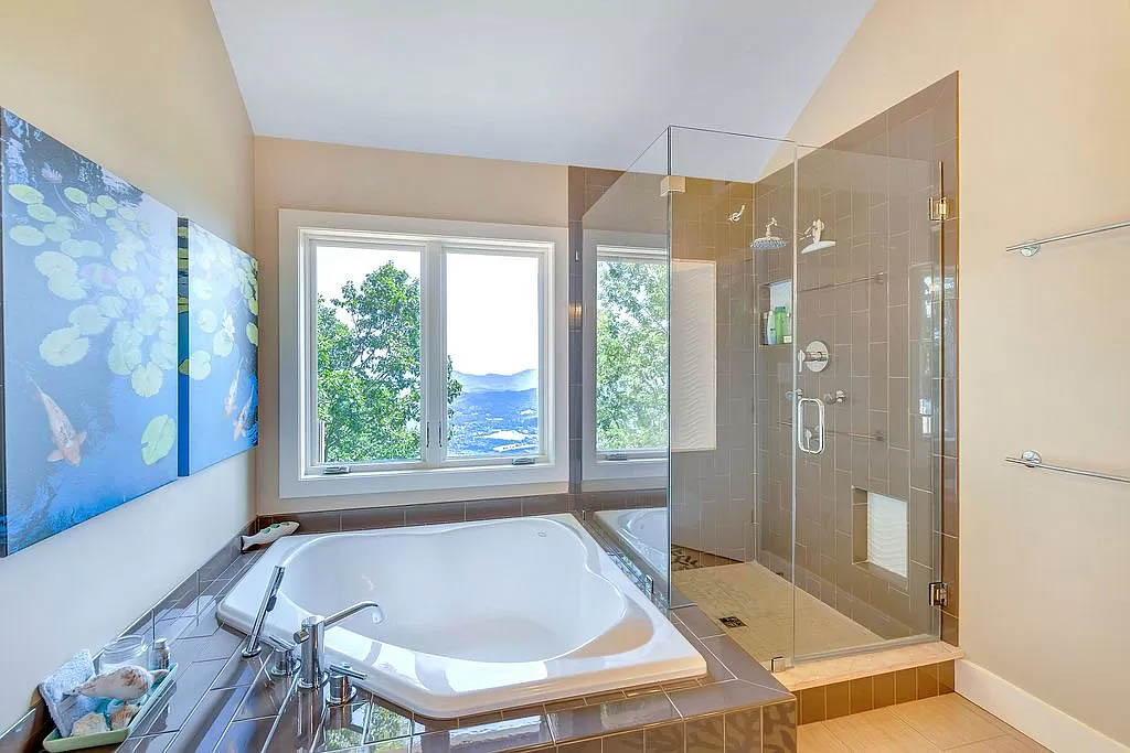 cotw mountain mama mia master bath with large jetted tub, glass walled shower and an wall of windows with a view