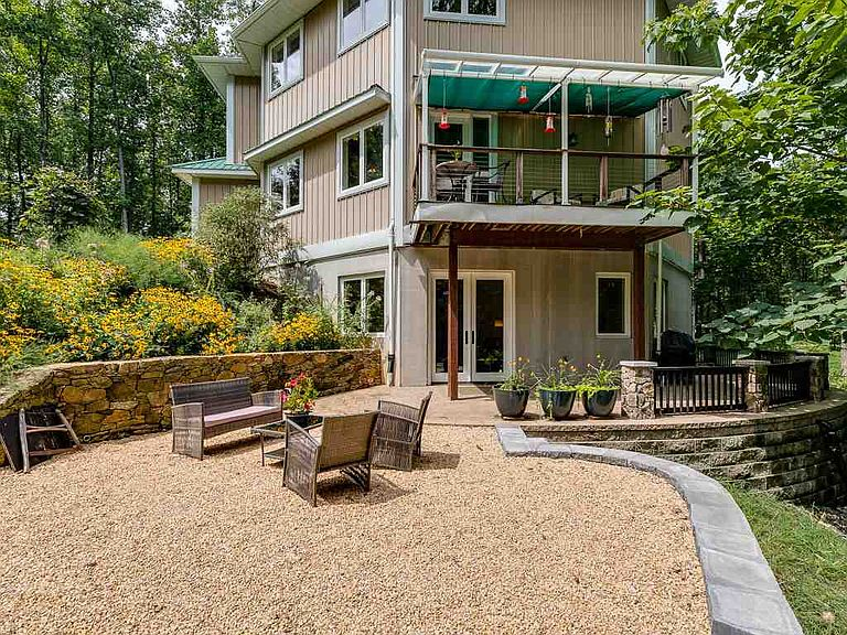 cotw welcome to the octagon back view of home with stone and gravel patios