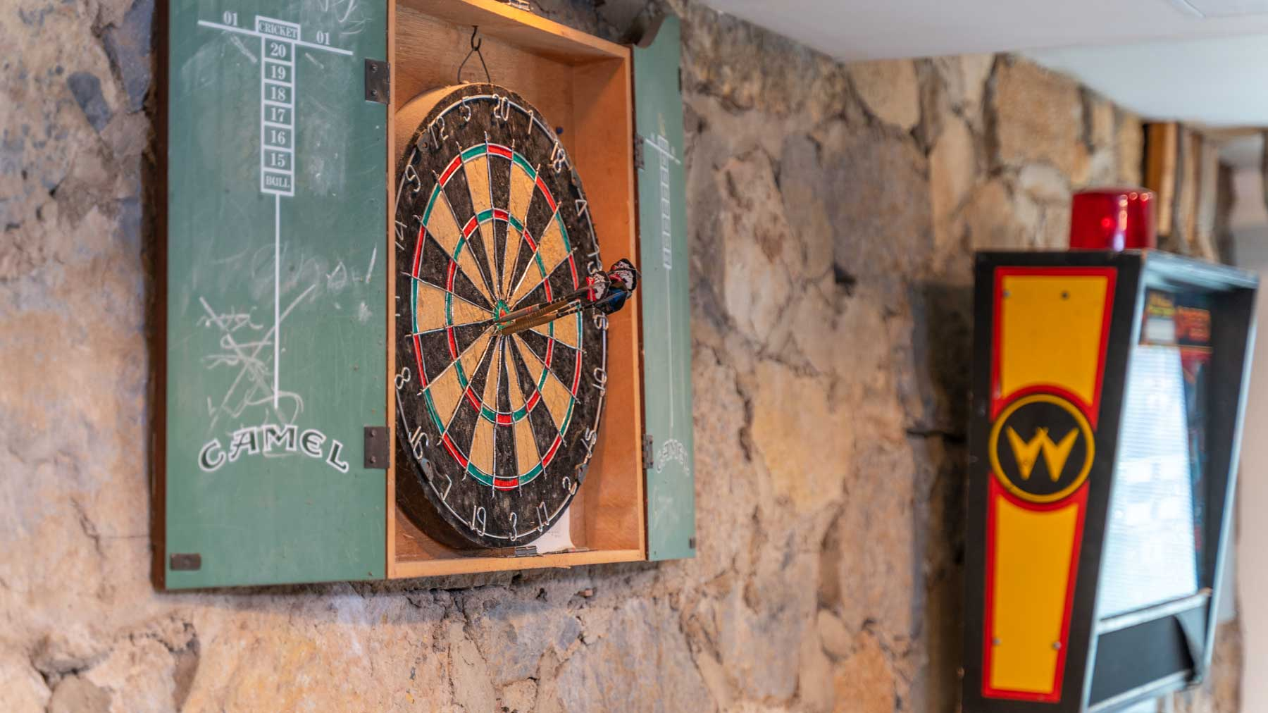Riverfront retreat basement stone wall and dart board