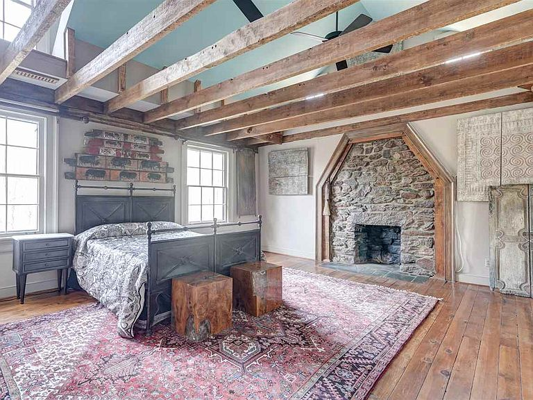 cotw modern antique master bedroom with vaulted ceiling exposed beams and stone fireplace