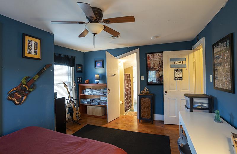 blue bedroom with wood floors