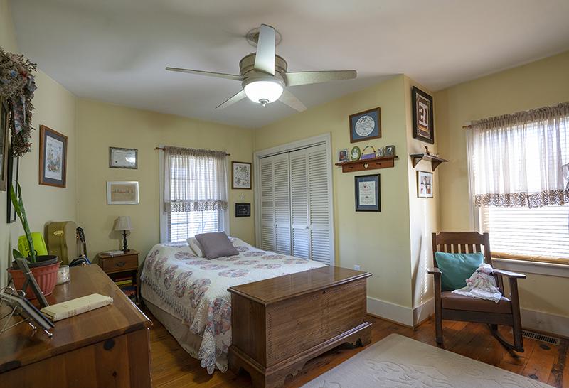 yellow bedroom with wood floors