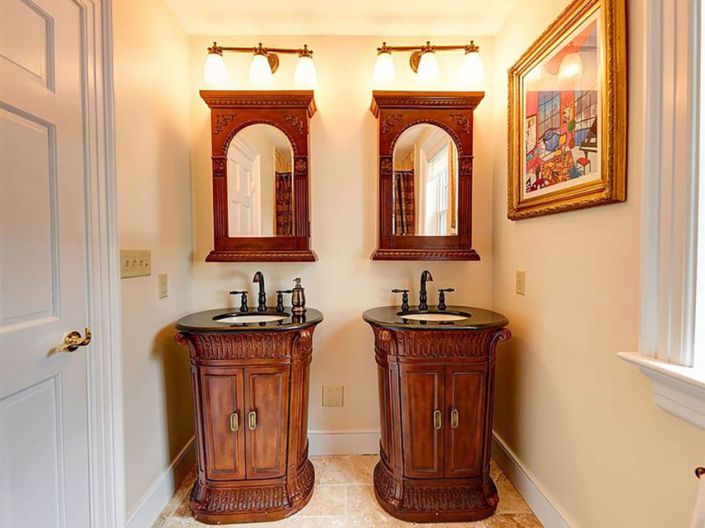 full bath with two separate cabinet vanities