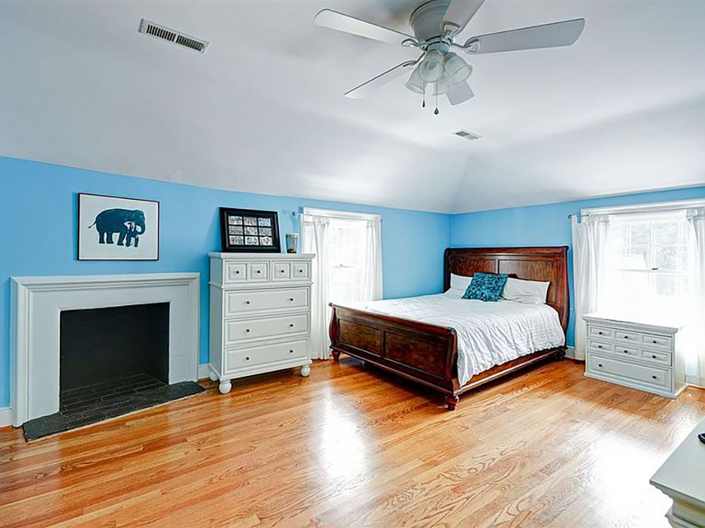 large upstairs bedroom with fireplace and tray ceiling