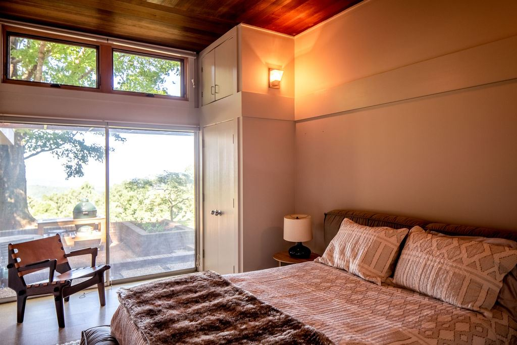 bedroom with wood ceiling and access to courtyard with mountain view