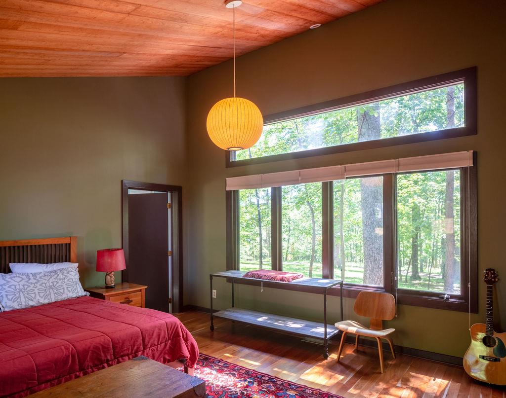guest house bedroom with wood ceiling and wooded view