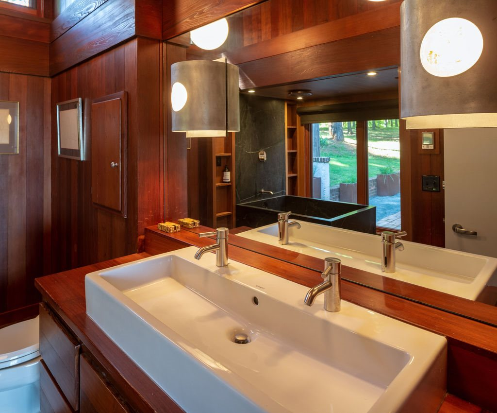 master bath with gorgeous wood paneling and large double faucet vessel sink