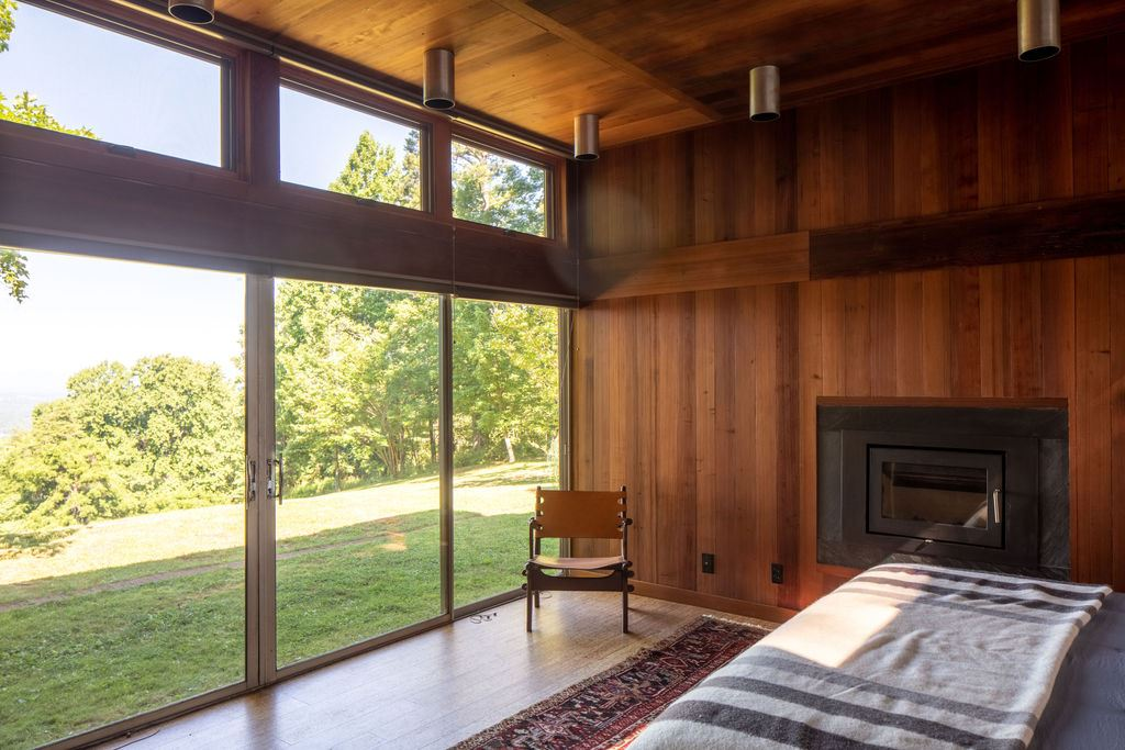 master bedroom with fireplace and wall of windows with mountain view and access to yard