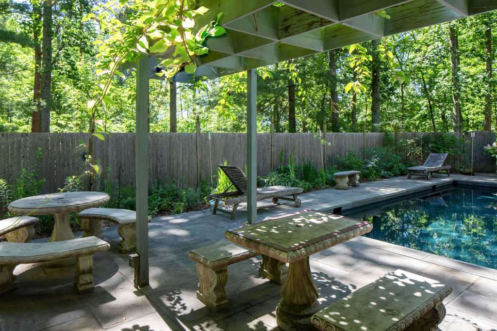 pool and arbor covered patio with cement picnic tables