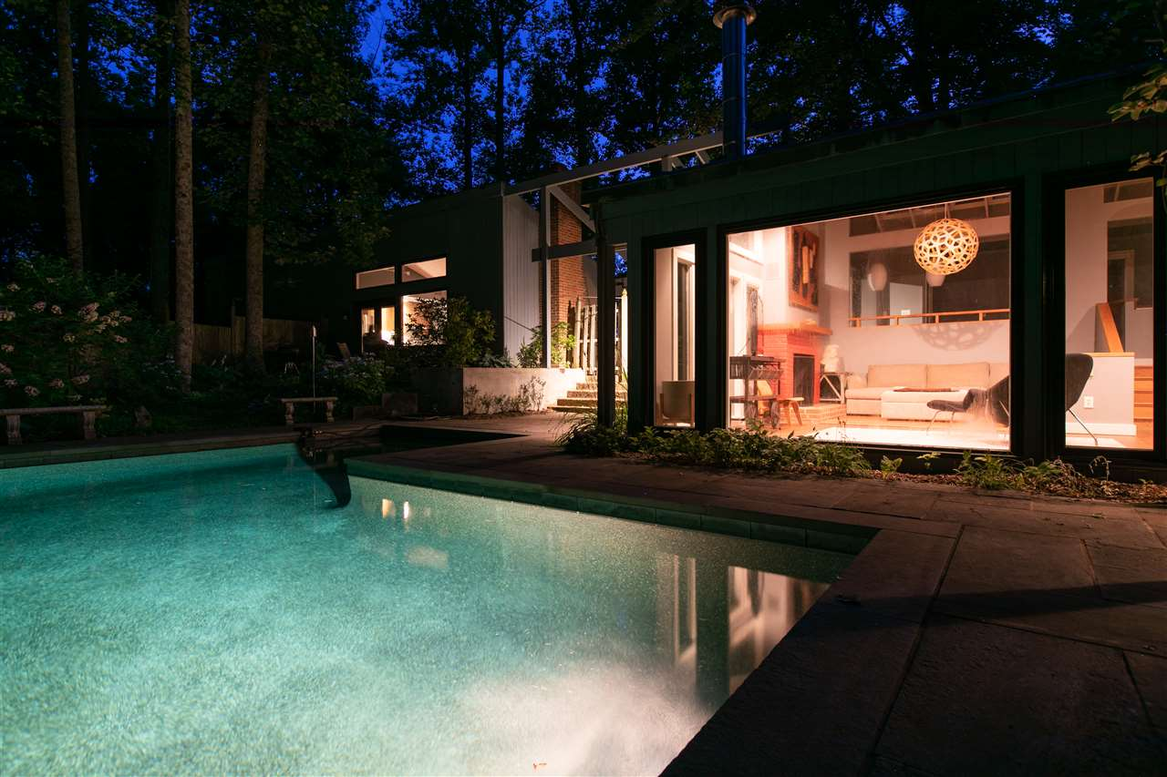pool lit up at night with guest house full wall of windows behind it