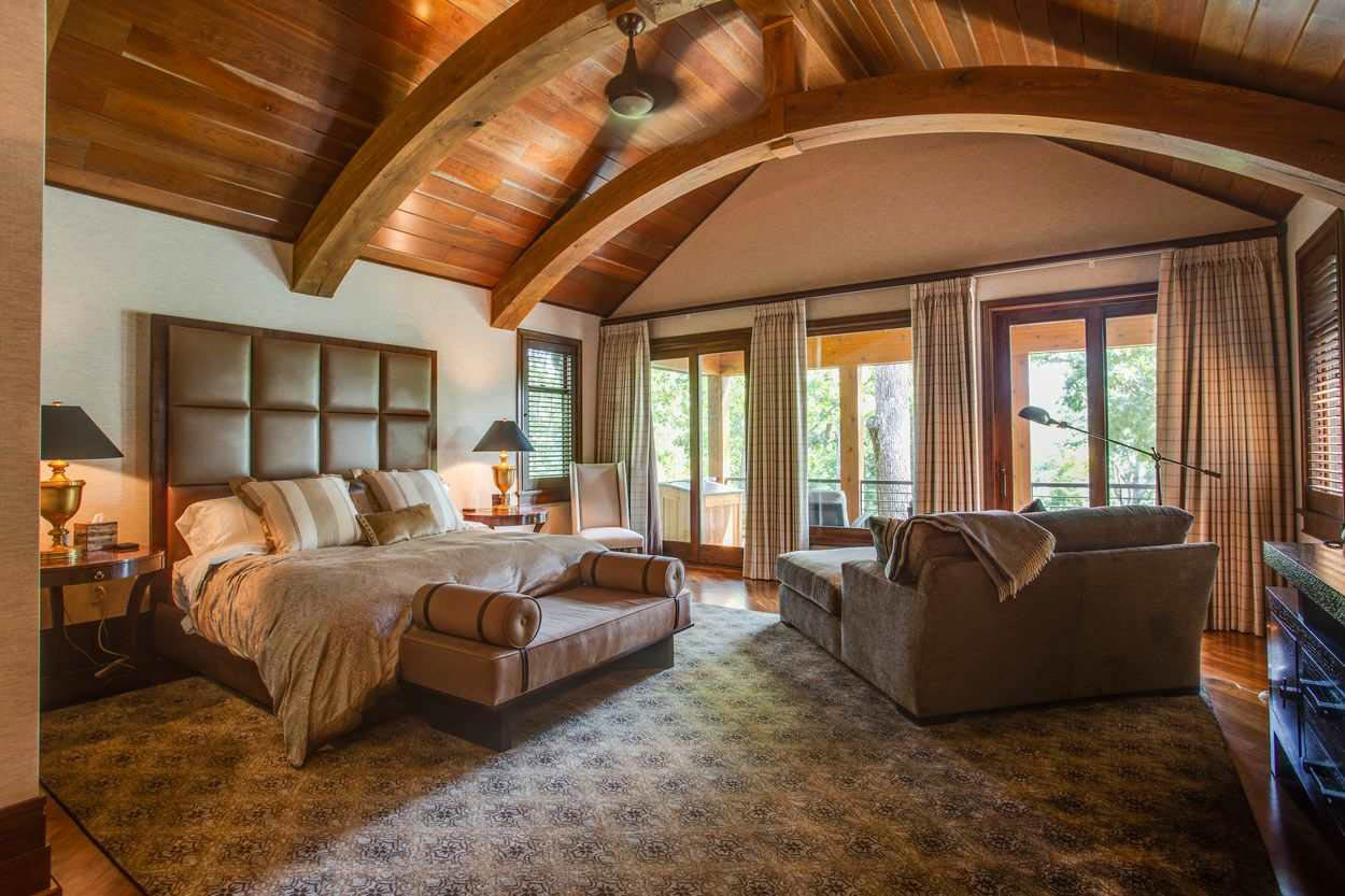 bedroom suite with wood arched beamed ceiling seating area and balcony
