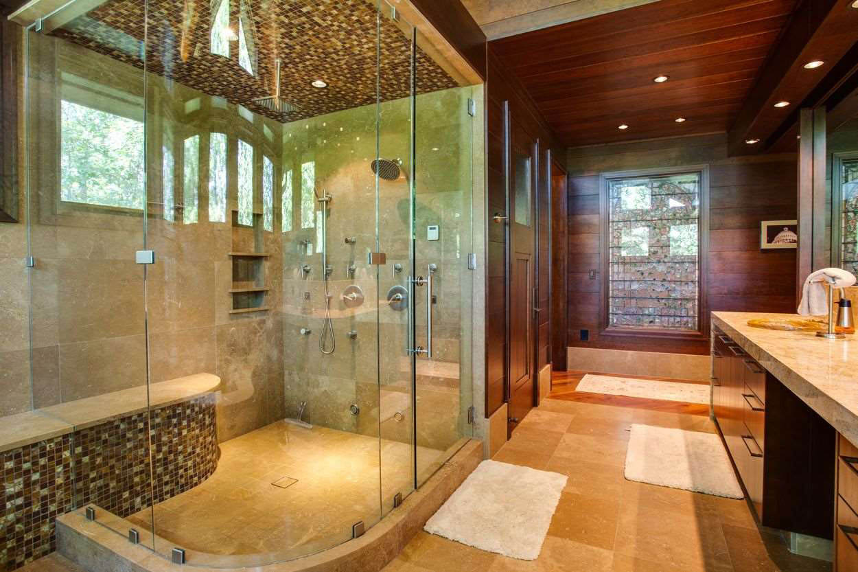 en suite bath with curved glass shower with bench