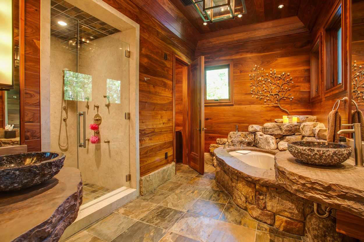 en suite bath with wood paneled walls and stone soaking tub and vanities with separate shower