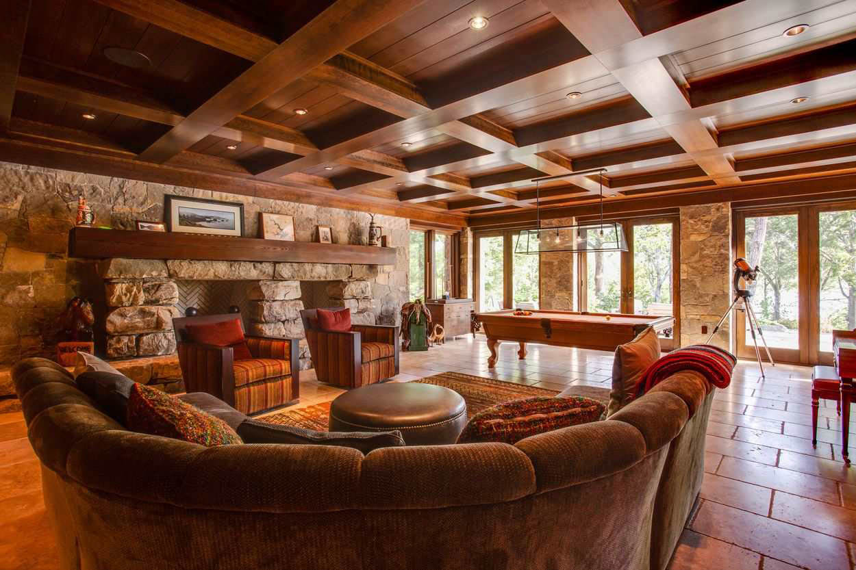gathering area with large stone fireplace wood paneled ceiling and doors to patio
