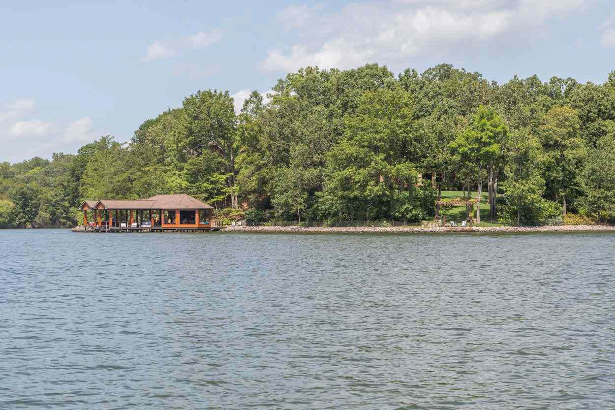 view of dock and wooded grounds from the water