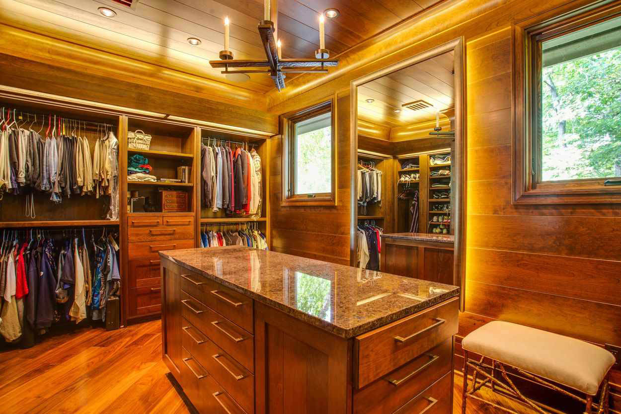 walk in closet with central island dresser and wood ceiling floors and closet system