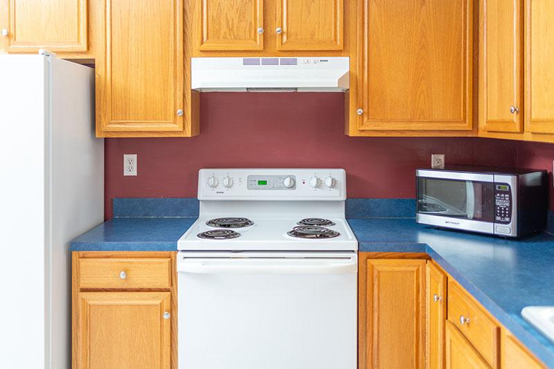 kitchen stove next to fridge